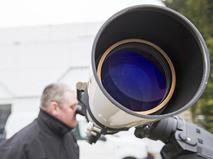 САстроном смотрит в телескоп