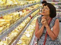 Женщина у прилавка с сырами в магазине