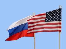 Государственные флаги России и США рядом на фоне голубого неба