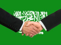 Мужчины пожимают руки на фоне флага Саудовской Аравии