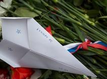 """Бумажный самолетик с надписью """"Су-24"""" и цветы в память о погибших военнослужащих в Сирии"""