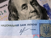 Денежные купюры долларов США и гривны Украины