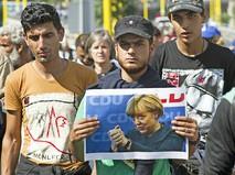 Мигранты с фотографией канцлера Германии Ангелы Меркель