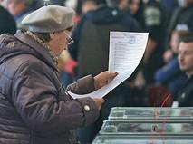 Женщина на избирательном участке в Киеве во время выборов в органы местного самоуправления