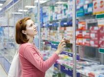 Молодая женщина у витрины с лекарствами в аптеке