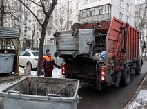 Сотрудник коммунальных служб выгружает мусор из контейнера