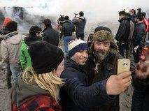 Мигранты фотографируются с жителями Франции