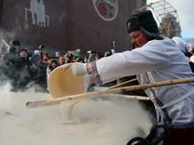 Участник масленичных гуляний во время установления рекорда по приготовлению самого большого блина России
