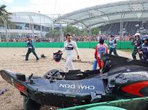 Автогонщик Фернандо Алонсо возле разбитого болида