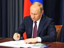 Президент России Владимир Путин подписывает указ