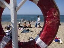 Отдыхающие на пляже Черного моря у детского оздоровительного лагеря