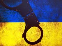 Наручники на фоне укранского флага