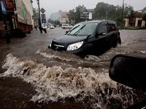 Автомобиль на затопленной дороге во время сильного ливня