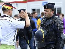 Сотрудник полиции Франции досматривает болельщика