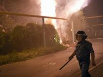 Полицейский во время столкновения с протестующими на улице близ захваченного в Ереване здания полка патрульно-постовой службы