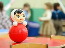 Игрушка-неваляшка на фоне играющих детей в детском саду