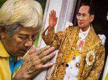 Житель Таиланда с портретом короля Пумипона Адульядета
