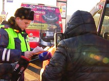 Сотрудник ДПС проверяет документы у водителя маршрутного микроавтобуса