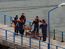 Спасатели несут тело погибшего в крушении самолета Минобороны РФ Ту-154 у побережья Черного моря в Сочи
