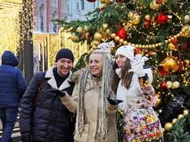 Люди фотографируются возле новогодней елки