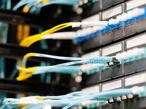 Оптические кабели, подключенные к панели в серверной комнате