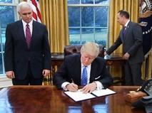 Дональд Трамп подписывает документ