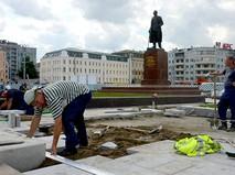 Рабочие кладут плитку на площади Тверская застава в Москве