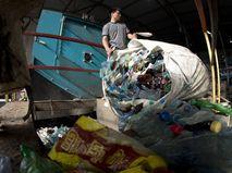 """Сотрудник завода высыпает в пресс отсортированные пластиковые бутылки в одном из цехов завода пластмасс """"Пларус"""" в Солнечногорске"""