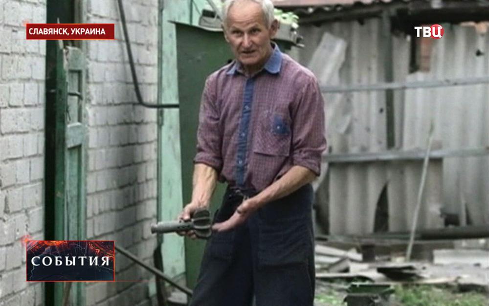 Житель Славянска показывает последствия минометного обстрела