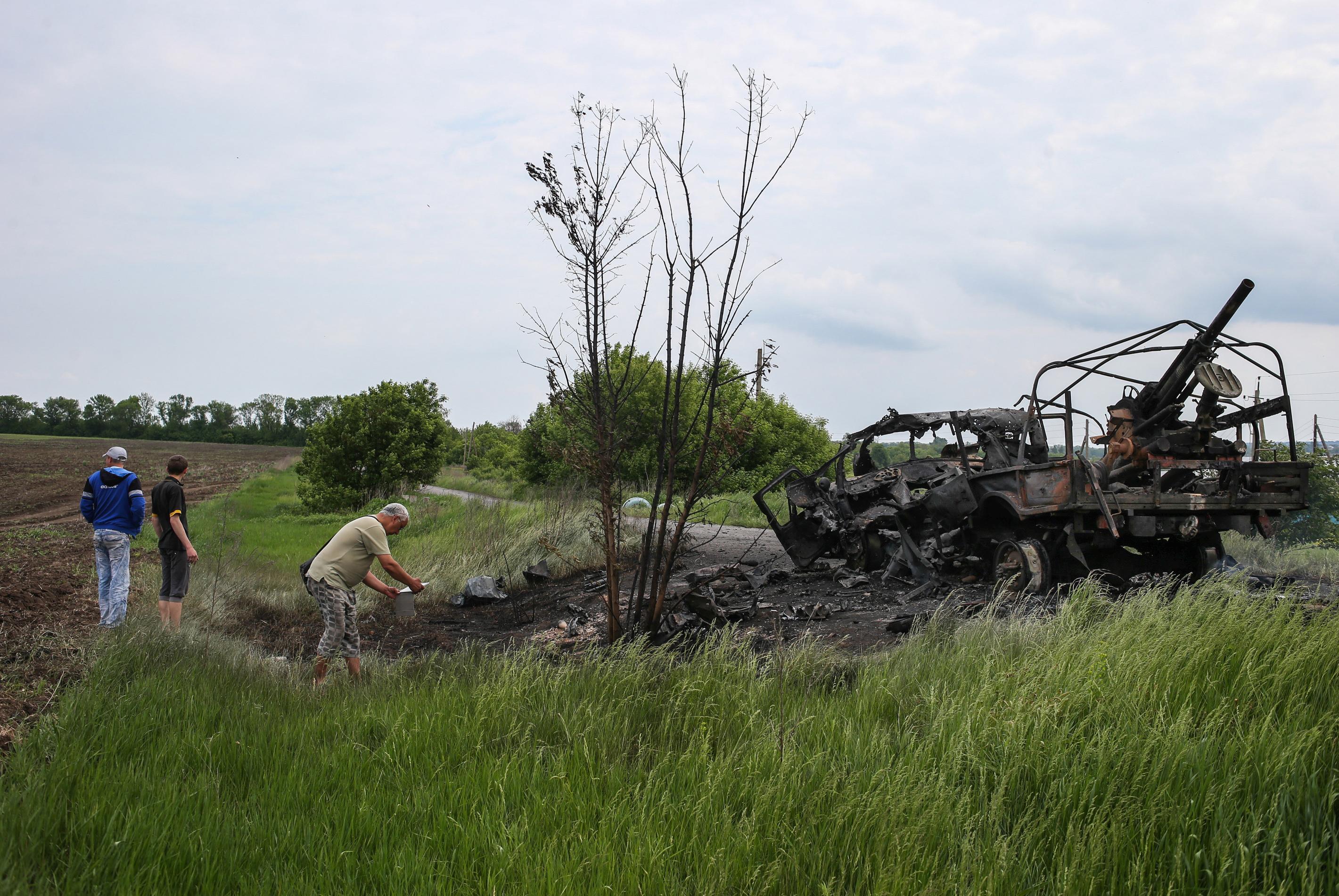 Местные жители возле сгоревшего военного автомобиля на месте вооруженных столкновений между народными ополченцами и украинскими военным