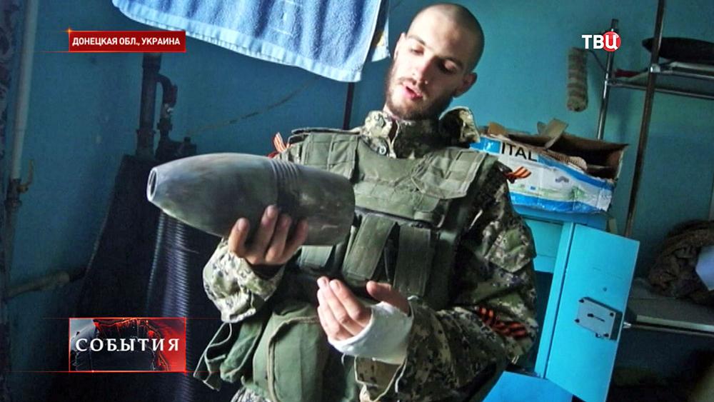 Боец народного ополчения демонстрирует танковый снаряд
