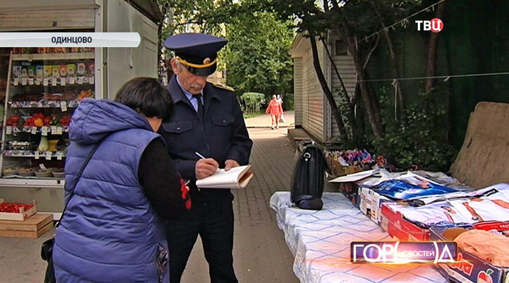 Инспектор Госадмтехнадзора выписывает штраф за незаконную уличную торговлю