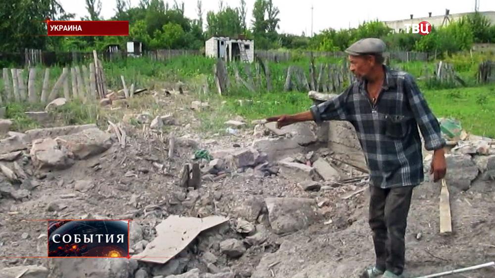 Житель востока Украины у разрушенного дома после обстрела