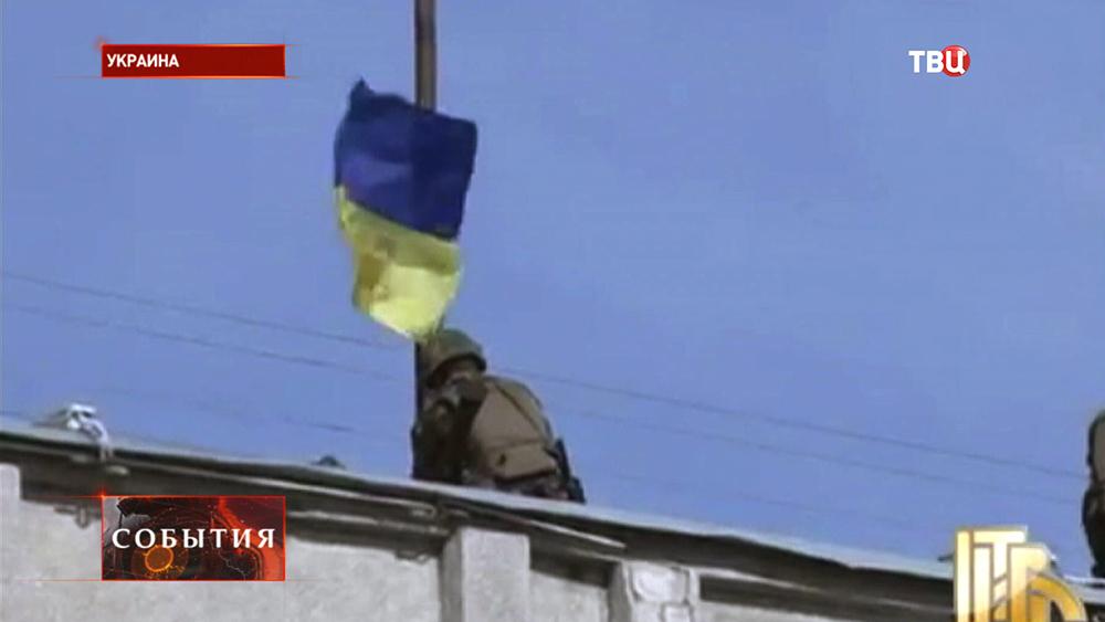 Солдат вешает Украинский флаг