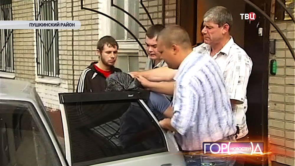 Подозреваемого в убийстве сажают в машину