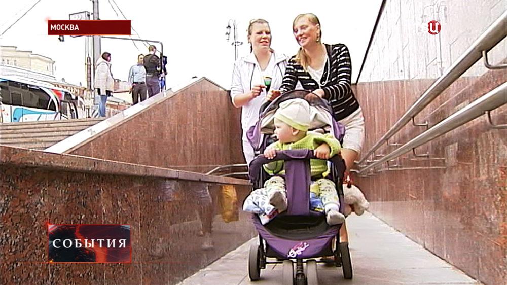 Мама с коляской спускается по пандусу