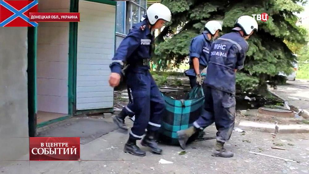 Спасатели выносят погибшие в результате обстрела Донецкой области