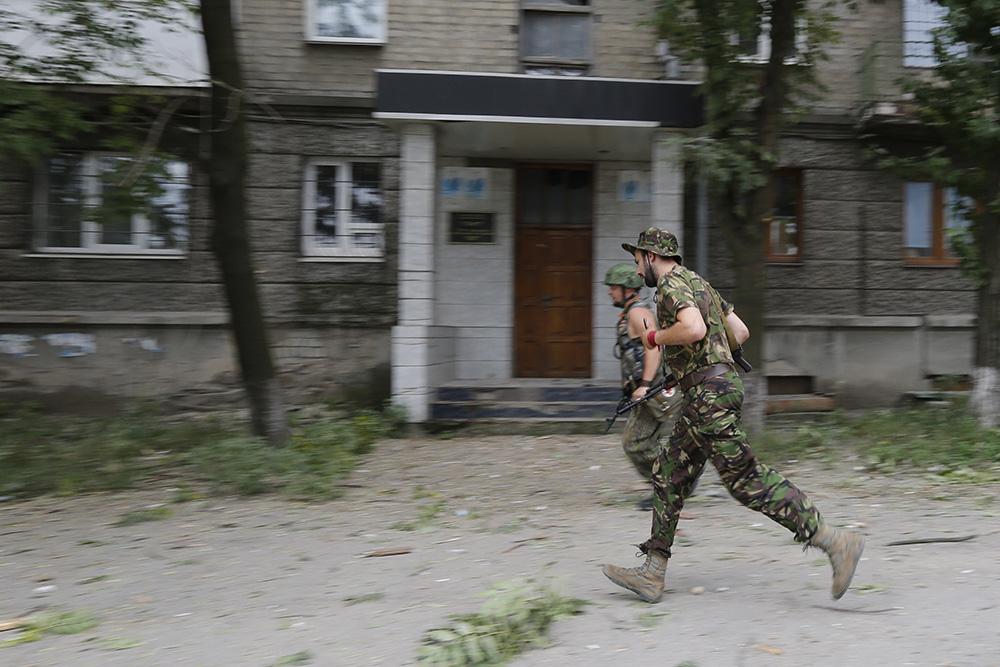 Народные ополченцы  на одной из улиц Луганска во время артобстрела