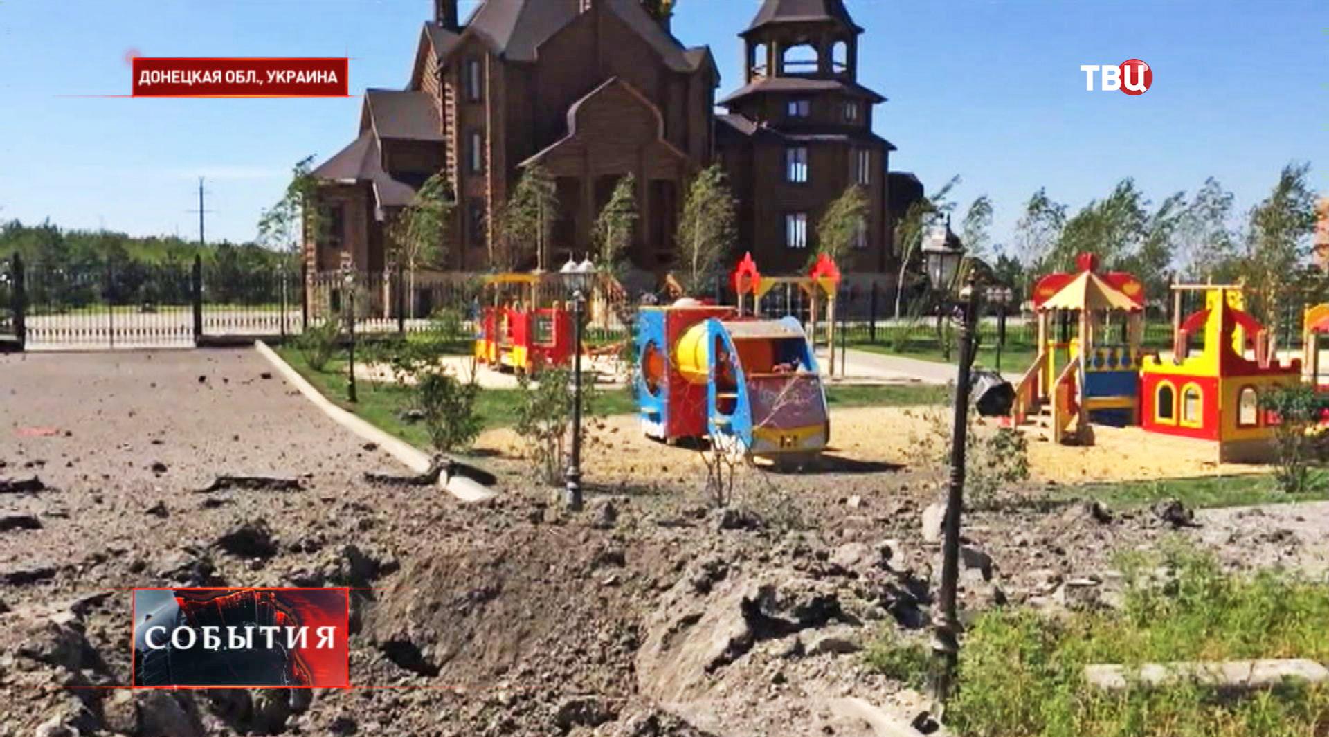 Воронка от разрыва снаряда на детской площадке