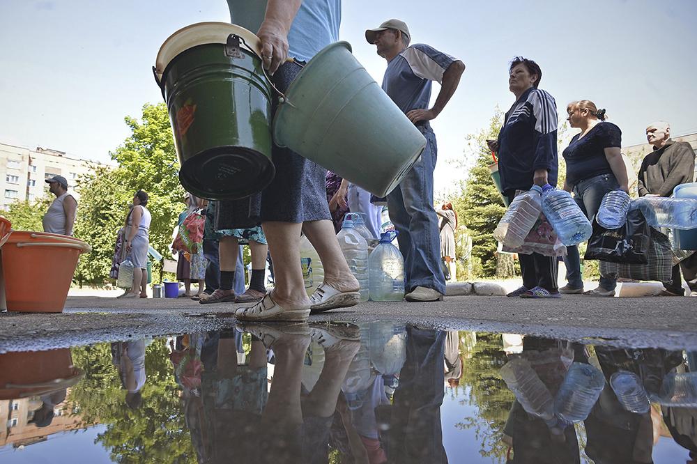 Местные жители в очереди за питьевой водой