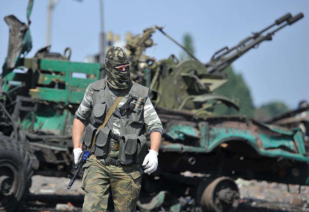 Народный ополченец около брошенной военной техники украинской армии