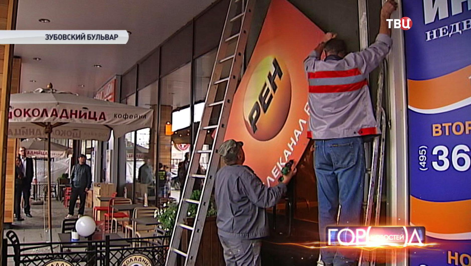 Рабочие снимают рекламные плакаты