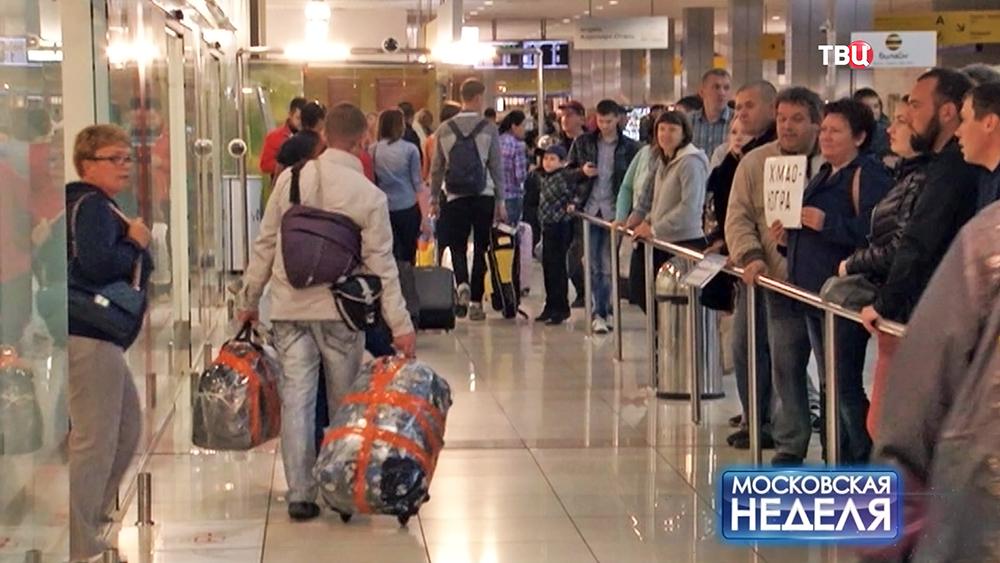 Туристы в зале прилета аэропорта