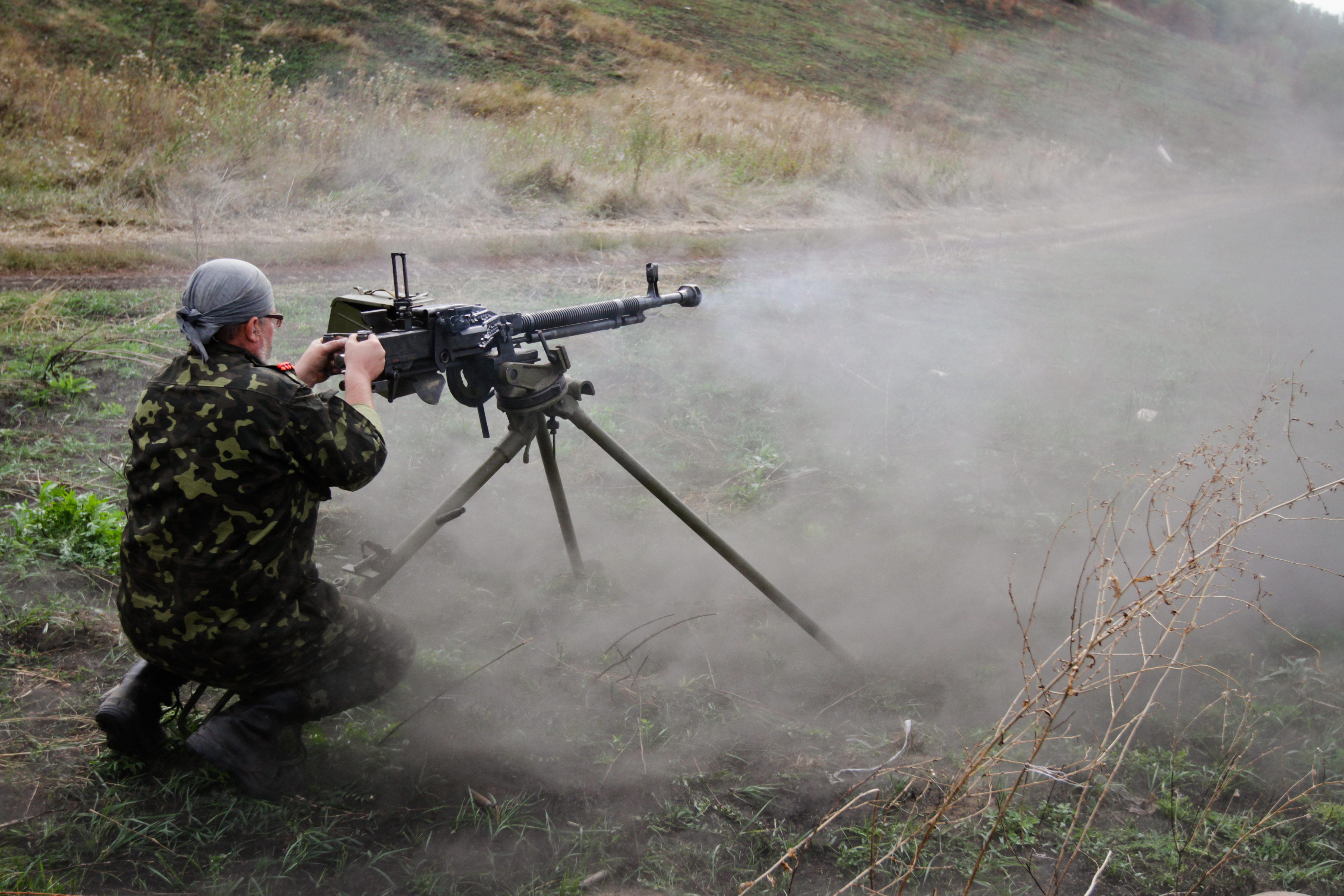 Солдат украинской армии ведет стрельбу из крупнокалиберного пулемета