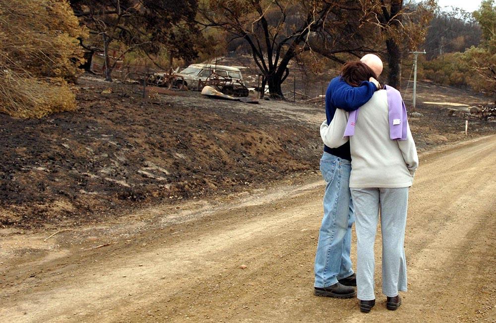 Жители Австралии возле сгоревшего дома