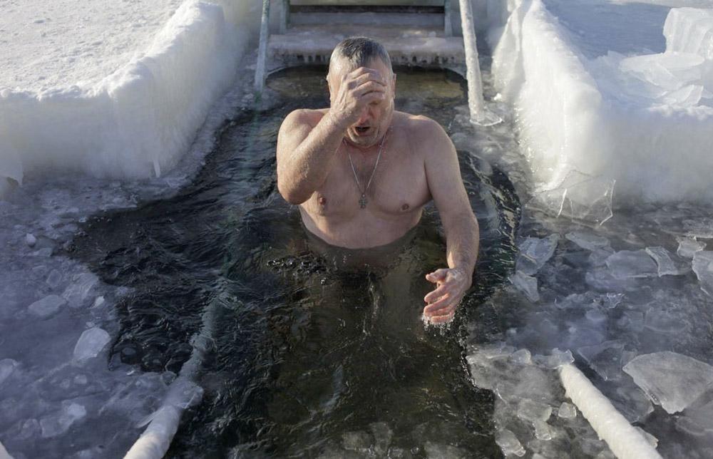 Верующий окунается в купели во время Крещенских купаний