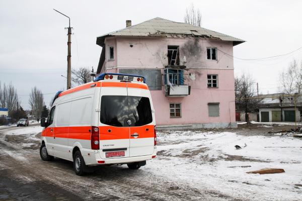 Автомобиль скорой помощи у пострадавшего от обстрела здания в Донецкой области