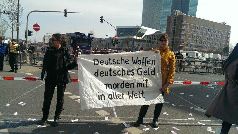 """Беспорядки во Франкфурте-на-Майне. Надпись на плакате: """"Немецкое оружие и немецкие деньги помогают убивать во всем мире"""""""