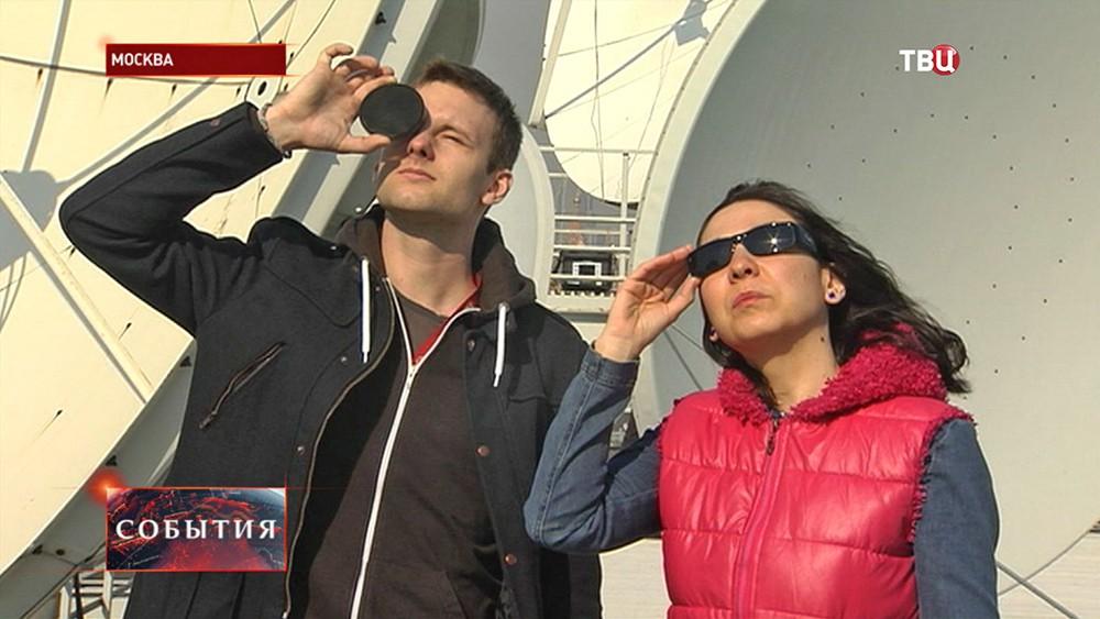 Люди наблюдают солнечное затмение
