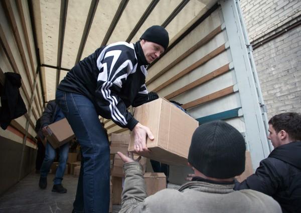 Разгрузка одного из грузовых автомобилей российского конвоя с гуманитарной помощью, прибывшего в Донецк